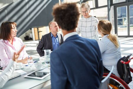 Senior woman as boss in a business meeting with a lecture or presentation Stock Photo