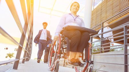 Woman with a wheelchair on a barrier-free ramp to access the wheelchair-accessible office