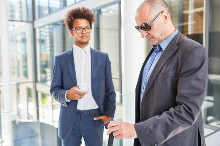 African business man talks to blind colleague as inclusion concept