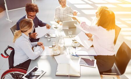 Inclusion among business people Meeting in the office with a woman in a wheelchair at the table during project planning