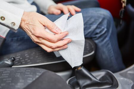 Hand disinfect the gear stick in the car with a kitchen towel Banque d'images