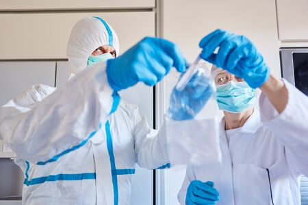 Saliva sample for Covid-19 test goes to the laboratory by employees in protective clothing Standard-Bild