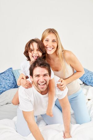 Parents silly with their son in bed in the morning in the bedroom 写真素材 - 143300966