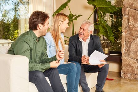 Happy couple as buyer or tenant together with estate agent at contract