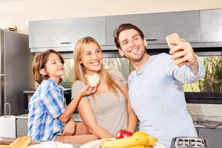 Happy father makes a selfie with smartphone from his family at breakfast