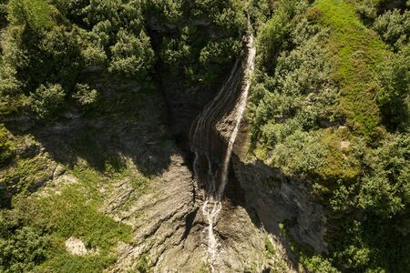 Aerial view of brook with tall waterfall in the French Alps