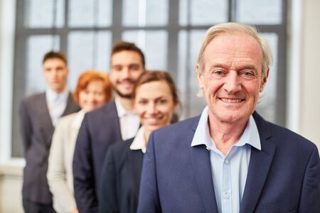 Smiling senior manager standing in front of business team group in the office