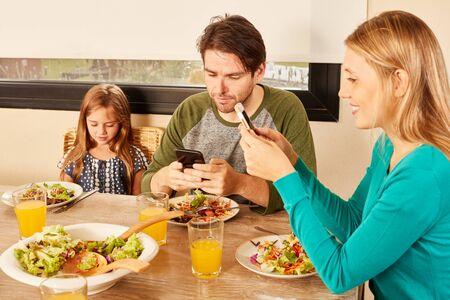 Parents et fille utilisant un smartphone et un téléphone portable ensemble à table au déjeuner Banque d'images