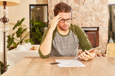 Worried man in financial planning or accounting is looking on a Tablet PC