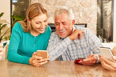 Woman shows senior a text message on the smartphone or explains the social media