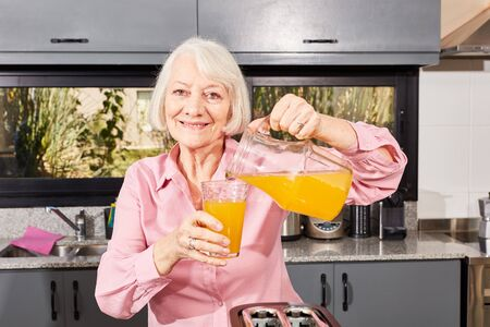 Smiling senior citizen pours orange juice from a carafe into a glass in the kitchen 스톡 콘텐츠