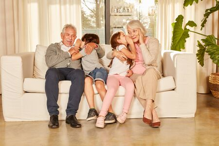 Grandchildren whisper a secret in the ears on the sofa at home to their grandparents
