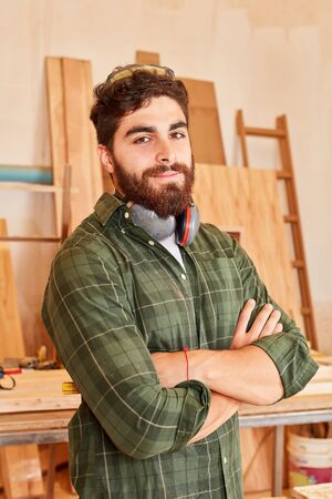 Young man as a proud carpenter or carpenter with crossed arms