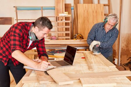 Carpenter team in the workshop during planning and woodworking