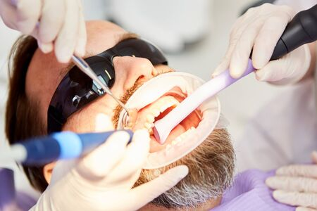 Dentist team in the treatment of patient while removing tartar and tooth decay