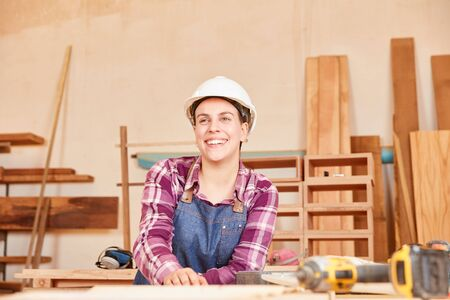 Young woman with hard hat as carpenter or joiner trainee in workshop