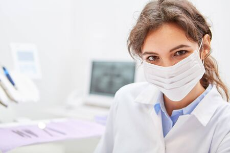 Young woman with surgical mask as a dentist or dental assistant in the practice