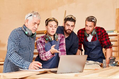 Young craftsman team and senior boss discuss a project idea on laptop 版權商用圖片 - 143598291
