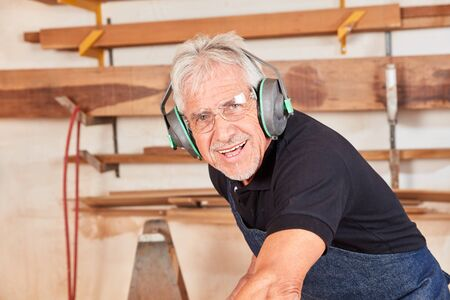 Smiling carpenter. Master with ear protection works on the circular saw in the workshop