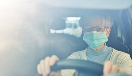 Elderly woman with a face mask driving a car as a risk group in the Covid-19 coronavirus epidemic