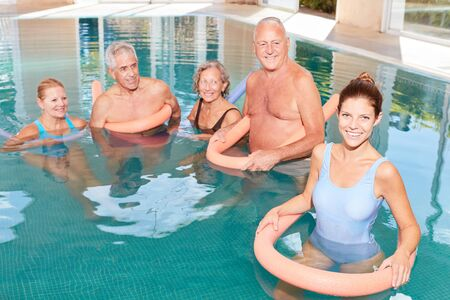 Young woman as a physiotherapist with seniors in an aqua gym class