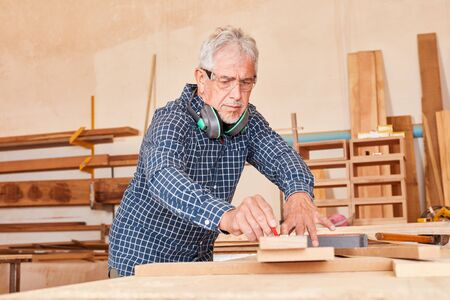 Experienced carpenter or carpenter at the workbench during the woodworking 版權商用圖片