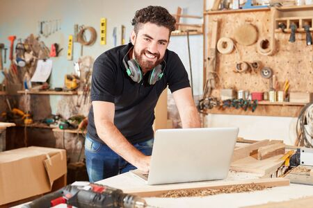 Young craftsman as creative start-up. Founder with laptop in a joinery 版權商用圖片