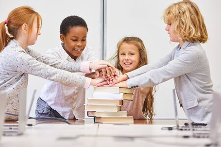 Group of children in elementary school stack hands for motivation in the classroom
