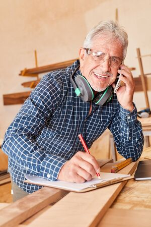 Senior craftsman with mobile phone notes appointments and clipboard makes appointments