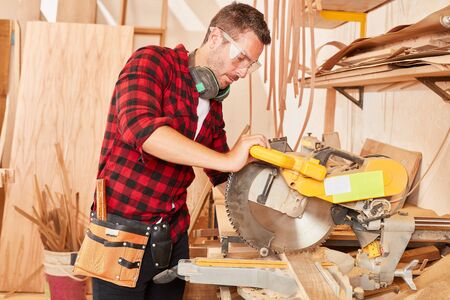 Man as carpenter trainee or apprentice at the chop saw in the carpentry workshop