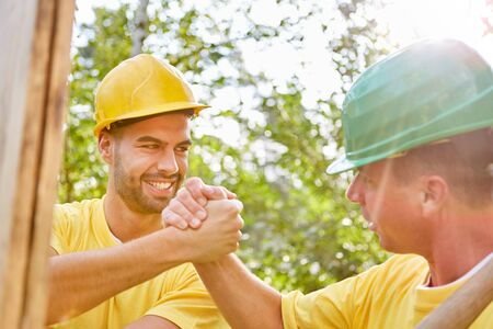 Happy artisans do teamwork on house building and hold hands