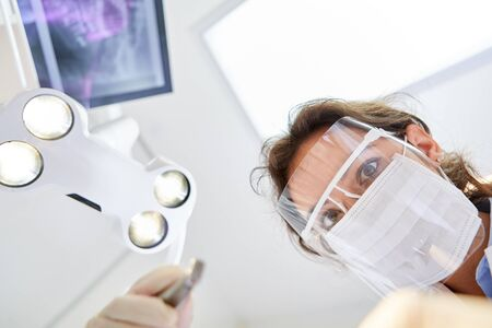 Young dentist with surgical mask and visor during a treatment or dental surgery in the dental clinic