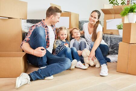 Family and children are sitting in a new apartment between many moving boxes when moving Foto de archivo