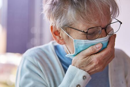 Elderly woman in quarantine mouthguard while coughing in the palm of her hand Foto de archivo