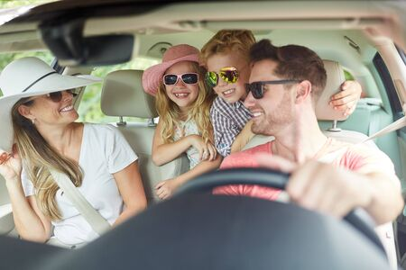 Family with two kids driving in summer vacation is having fun