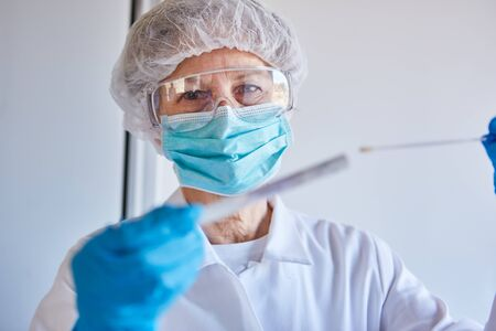 Smear test of saliva for Covid-19 rapid test with medical professionals in the laboratory during a coronavirus epidemic Standard-Bild