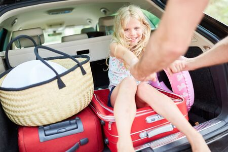 Cheerful girl is sitting on luggage in the car trunk before traveling on vacation