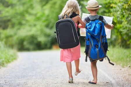 Two kids with backpack and map hiking together in nature