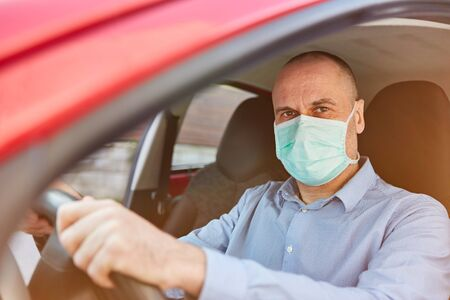 Senior with face mask while driving in Covid-19 coronavirus pandemic Banque d'images