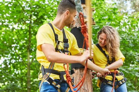 Woman and man in the high ropes course help themselves with the protection in teamwork
