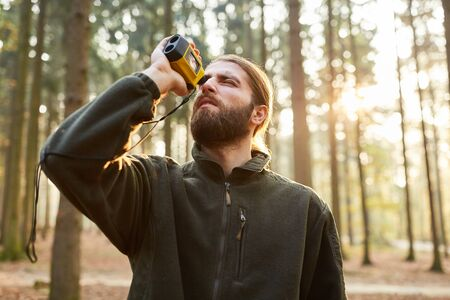 Forester determines the tree height with a laser rangefinder in the forest