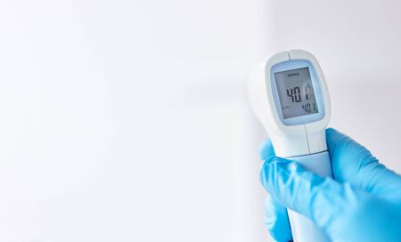 Infrared clinical thermometer shows fever after measurement in Covid-19 coronavirus epidemic