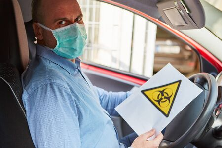Biohazard driver warning of Covid-19 coronavirus pandemic Stock Photo