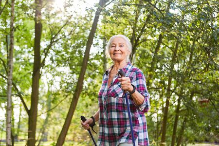 Sporty senior woman trains endurance while Nordic walking in nature