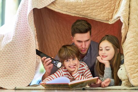 Father is reading an exciting story from a book to his children