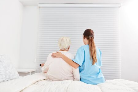 Young caregiver helps elderly woman out of bed in nursing home