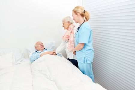 Old woman visits her husband in hospital with the help of a caregiver Stock Photo