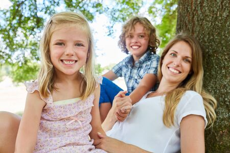 Happy family with mother and two children sit relaxed under one Фото со стока
