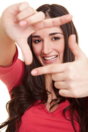 Young laughing woman holds her hands as a frame