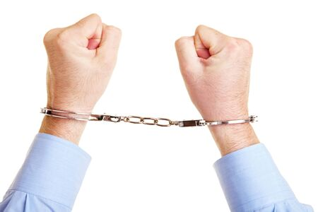 Two hands in handcuffs are clenched into fists